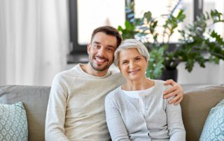 elderly woman with adult family member smiling