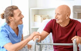 Elderly man with caregiver in nursing home