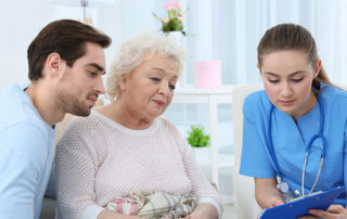Nurse talking with grandmother and her grandson indoors