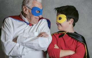 Grandfather With Grandson dressed as a superhero on gray background
