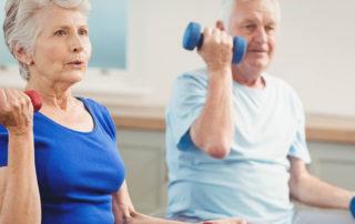 Senior couple sitting on fitness balls with dumbbells